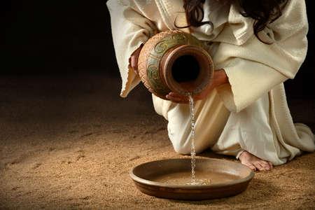 sirvientes: Jesús verter agua de una jarra a la sartén a lavar los pies de los discípulos Foto de archivo