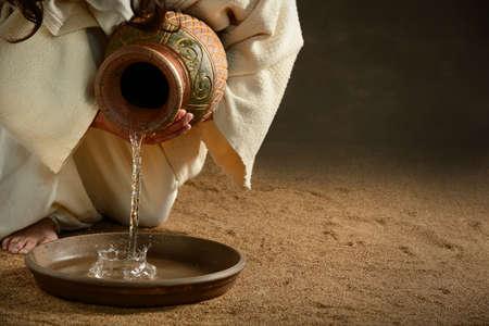Jesus gießt Wasser aus Krug auf einem dunklen Hintergrund