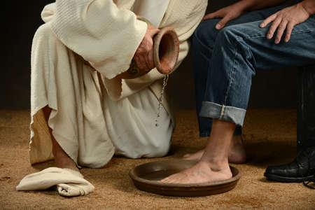 현대 사람이 청바지를 입고 예수의 발을 씻기 스톡 콘텐츠