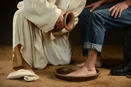 Jesús lavando los pies del hombre moderno vistiendo jeans Foto de archivo