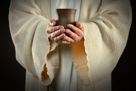 De handen van Jezus die wijn beker, symbool van communie