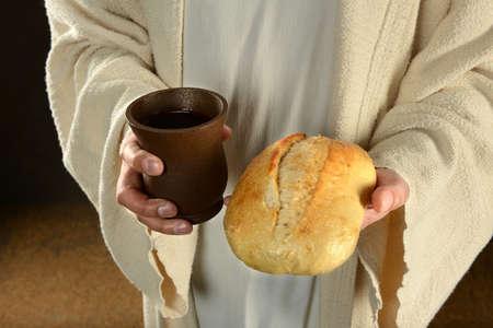 暗い背景上にパンとワインを置くイエス ・ キリストの手 写真素材
