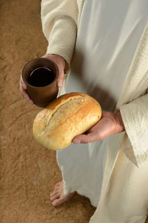 Jesus hands holding bread and cup of wime photo