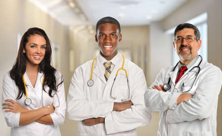 Group of three diverse doctors with arms crossed inside hospital building