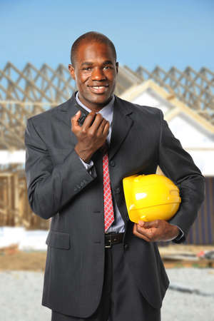 African American construction manager holding hardhat and radio at building site
