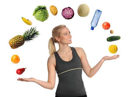Mooie jonge vrouw jongleren fruit, groenten en een fles water geïsoleerd over witte achtergrond