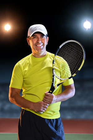 raquet: Portrait of Hispanic senior player holding raquet standing on tennis court