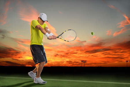 Hispanic tennis player hitting ball during sunset