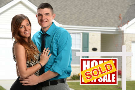 purchased: Young couple in front of newly purchased home