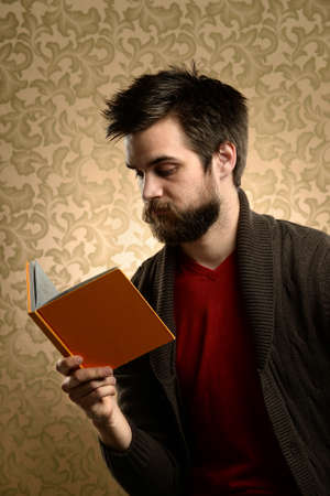 Young man with beard reading book over retro background photo