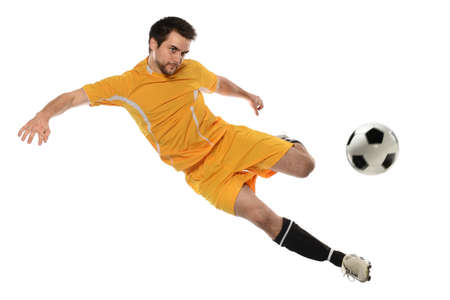 kicking ball: Young soccer player kicking ball isolated over white background
