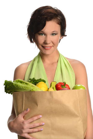 woman holding bag: Portrait of beautiful young woman holding bag of groceries isolated over white background