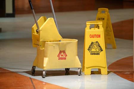 Hausmeister Mopp und Vorsicht Zeichen auf Flur