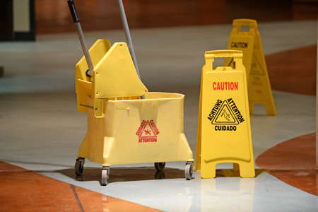 mopped: Janitorial mop and caution sign on hallway Stock Photo