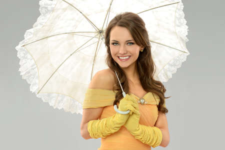 Young woman in Victorian dress holding umbrella isolated over neutral background