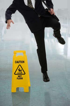 Empresario resbalones en suelo mojado delante del signo de precaución en el pasillo Foto de archivo - 31137422