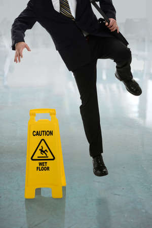 Businessman slipping on wet floor in front of caution sign in hallway Stockfoto