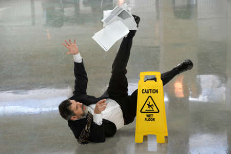 hombre cayendose: Hombre de negocios mayor que cae sobre suelo mojado delante del signo de precaución Foto de archivo