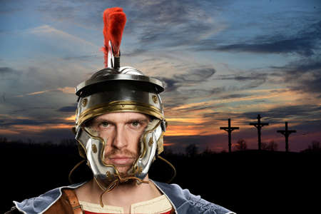 Portrait of Roman soldier with crossed in background at sunset Stock Photo