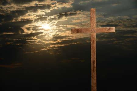 Houten kruis tijdens zonsondergang met hoge constrastlichten en schaduwen