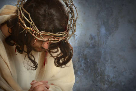 Jesus with crown of thorns with head down over old wall photo