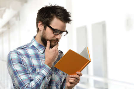 Portrait of young man with beard reading inside\ building