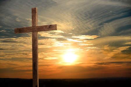 色鮮やかな夕焼けを木製の十字架