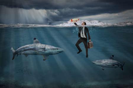 嵐の海でサメの間で泳いで実業家と競争力のある事業コンセプト 写真素材