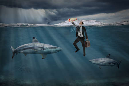 Competitive busines concept with businessman swiming among sharks in stormy seas