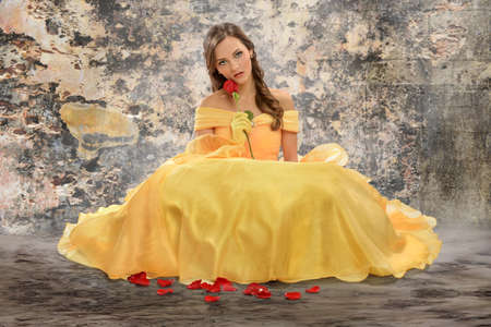 victorian lady: Beautiful young woman dressed in Victorian dress holding rose Stock Photo