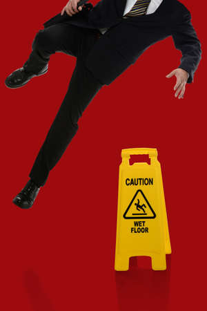 Businessman slipping on wet floor in front of caution sign over red background photo