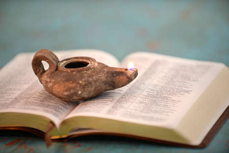 Ancient Israelite oil lamp on open Bible over vintage table Banque d'images