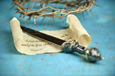 Bible concept of Ephesian 6:1 with sword; scroll; and crown of thorns on vintage table Stock Photo