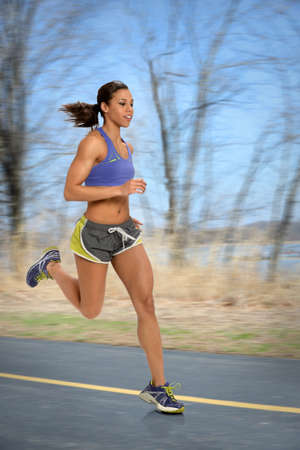 exercises: African American woman running outdoors