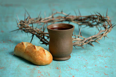 Bread, cup of wine and crown of thorns on old table