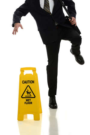 Businessman slipping on wet floor in front of caution sign isolated over white background photo