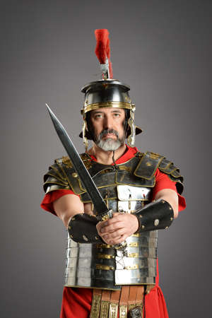 Portrait of Roman centurion holding sword over a neutral background