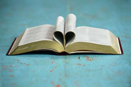 ビンテージ テーブルの開いている聖書によって形成された心 写真素材