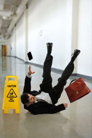 wet suit: Mature businessman falling on wet floor inside building hallway