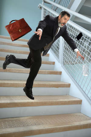tripping: Senior businessman falling on stairs in office building