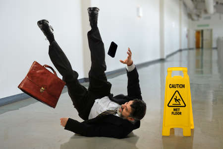hombre cayendose: Hombre de negocios mayor que cae cerca de signo de precaución en pasillo Foto de archivo