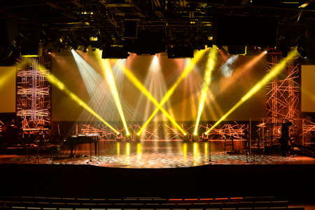 Stage lights before start of concert with multiple musical instruments and microphones
