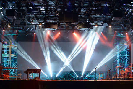 Concert lights on stage with assortment of musical instruments Editorial