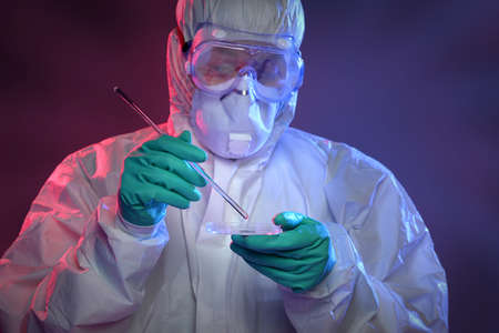 hazmat: Scientist in Hazmat suit and protective gear working with virus on Petri dish Stock Photo