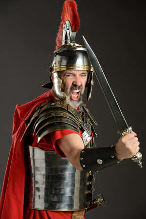 Portrait of Roman Centurion brandishing sword over neutral background