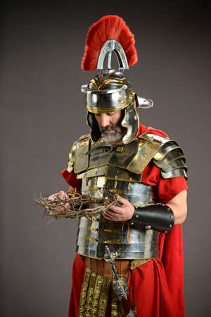 Roman soldier holding crown of thorns over neutral background Stock Photo