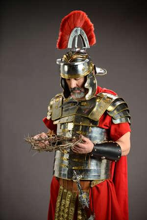 cascos romanos: Romano soldado sosteniendo una corona de espinas sobre fondo neutro