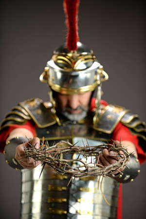 Roman soldier holding crown of thorns - With selective focus on foreground Stock Photo