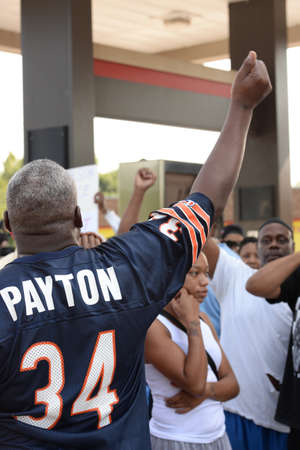 reacts: FERGUSON, MOUSA – AUGUST 15, 2015: Man at the Site of Quick Trip reacts to Police Chief Thomas Jackson release of the name of the officer that shot Michael Brown.