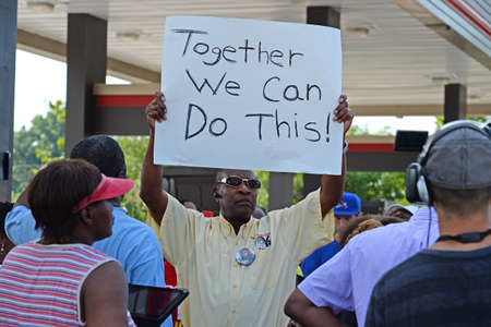 demonstrators: FERGUSON, MOUSA – AUGUST 15, 2015: Man at the Site of Quick Trip Holds sign after Police Chief Thomas Jackson release of the name of the officer that shot Michael Brown.